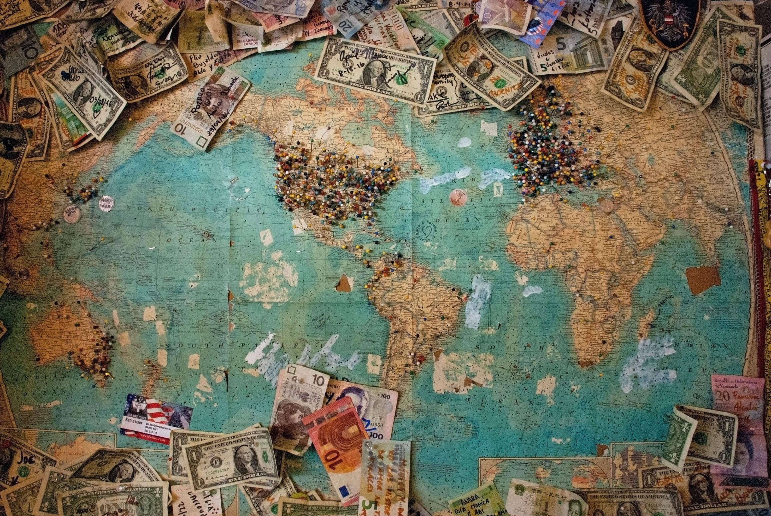 """Of the image the photographer said: """"During our road trip on highway 66 we stopped at a local shop and I spotted in a dark corner this old map with pins and currencies left by visitors from all over the planet."""""""